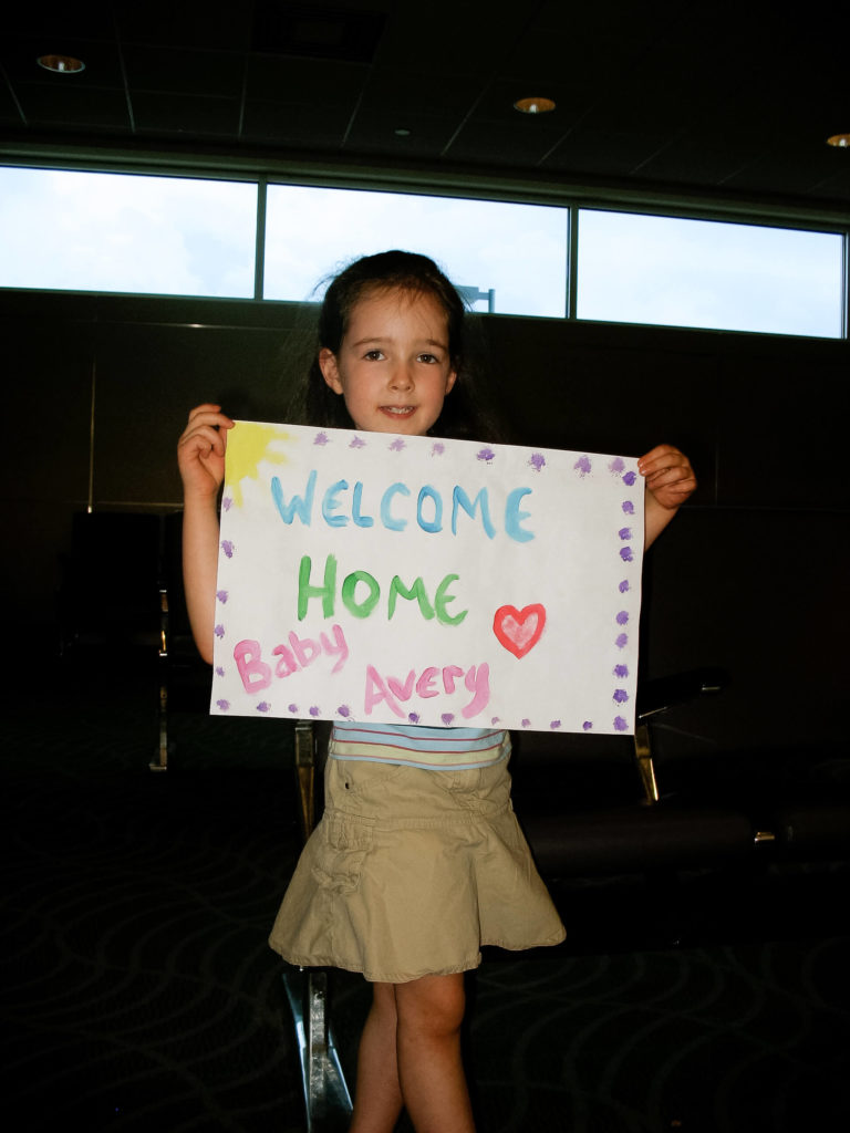 older sister holds painted sign that says 'welcome home baby avery'