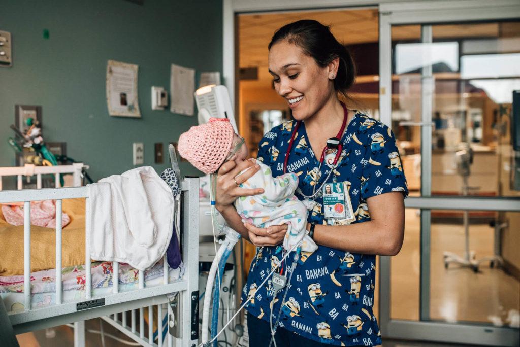 nurse smiles as she holds newborn