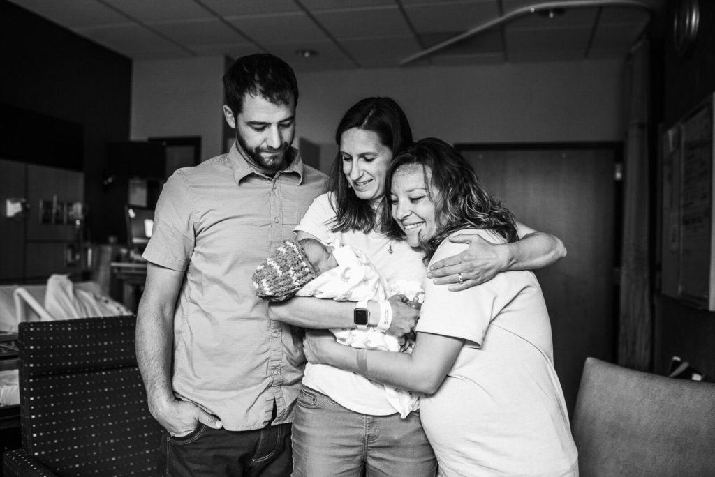 three family members huddle around newborn