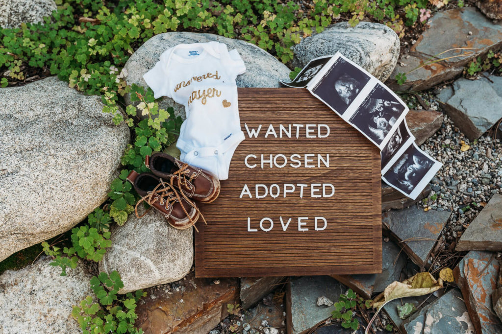 sign that says 'wanted chosen adopted loved' with baby photos, shoes, and onesie