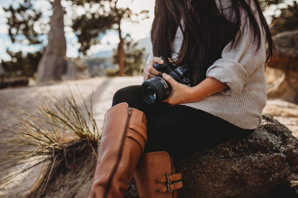 woman holding camera and wearing tall brown boots