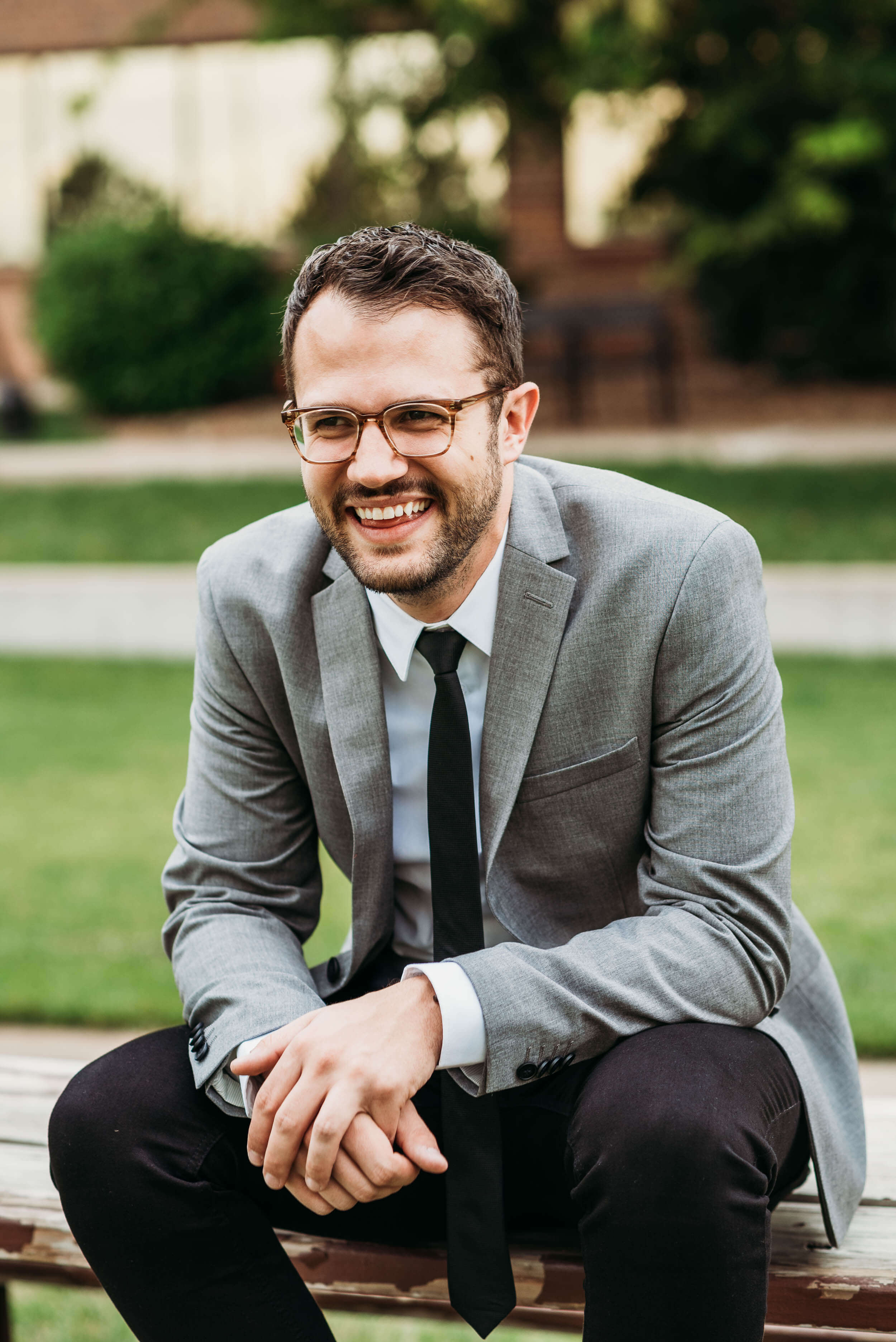 groom sitting on bench smiling
