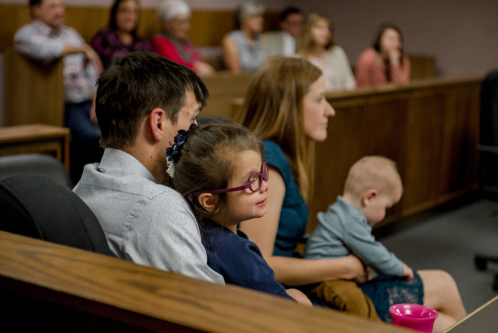 family sitting on court pew